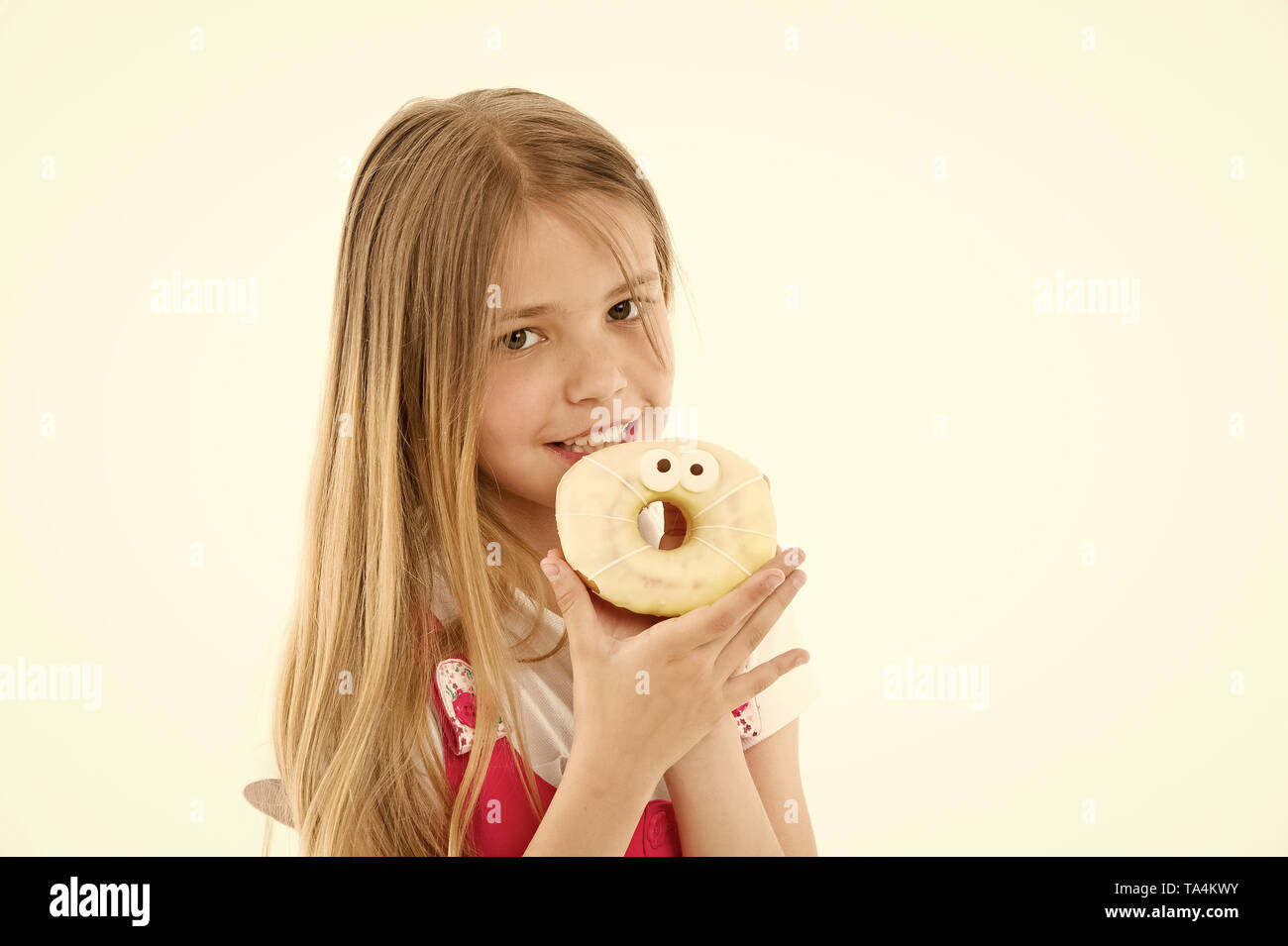 Child eat donut isolated on white. Little girl with glazed ring doughnut. Kid with junk food. Food for snack and dessert. dieting and fitness concept. Childhood and childcare, copy space. - Stock Image