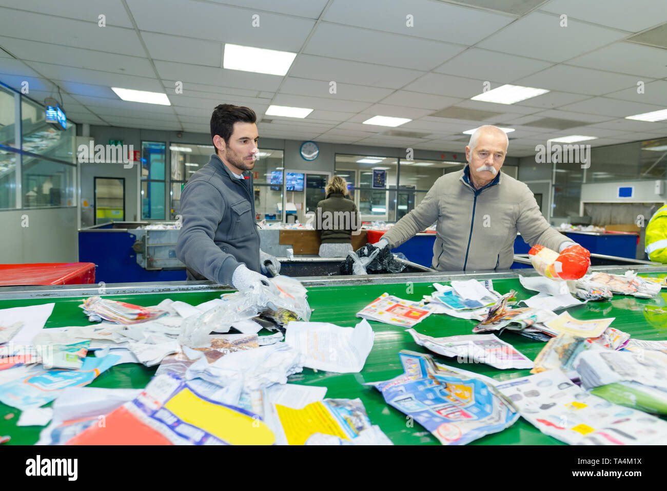 workers sorting through paper waste in recycling center - Stock Image