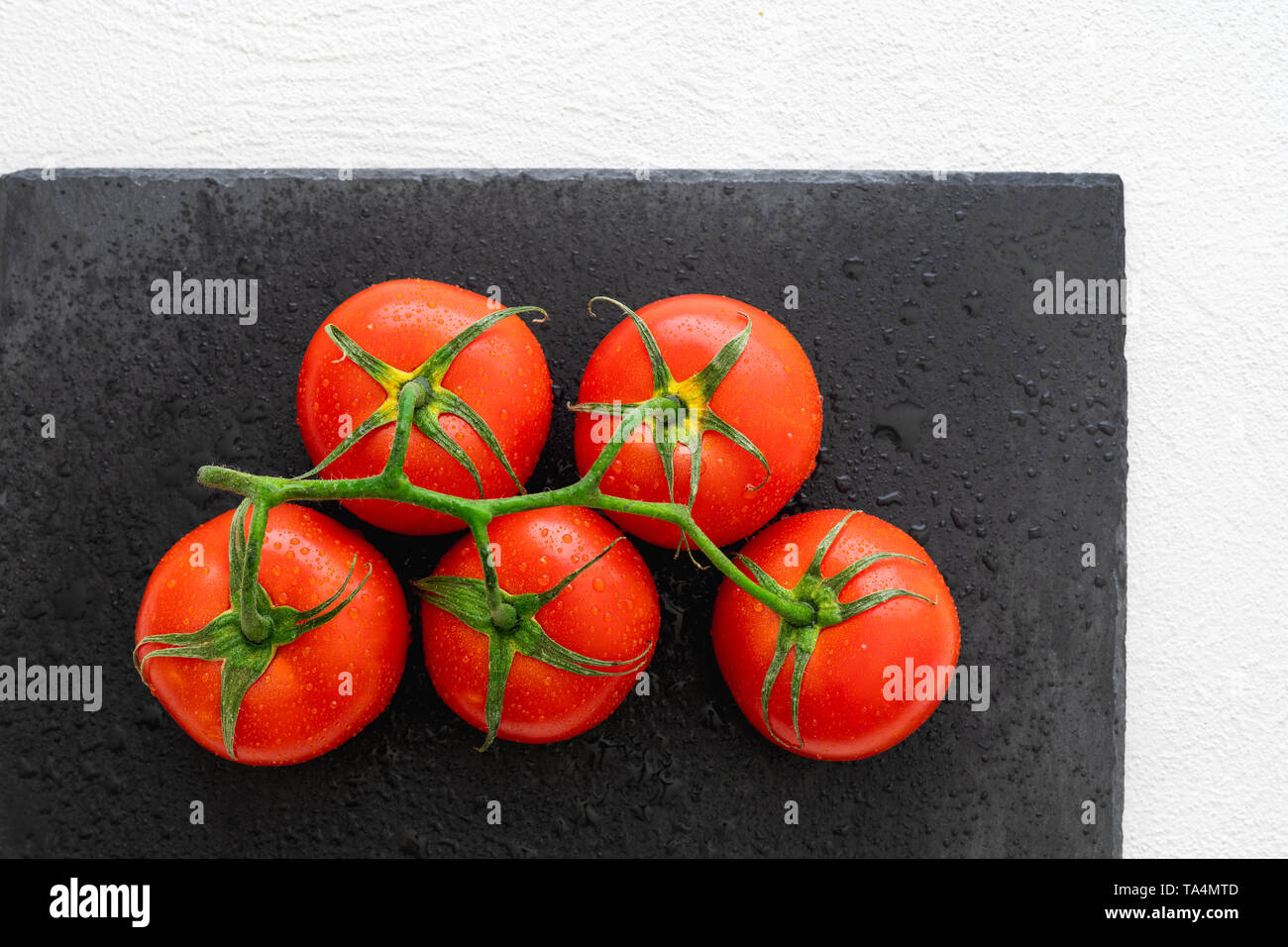 Fresh Red Tomatoes With Drops of Water on a Black Chopping Board in White BackgroundClose Up, Top View - Stock Image