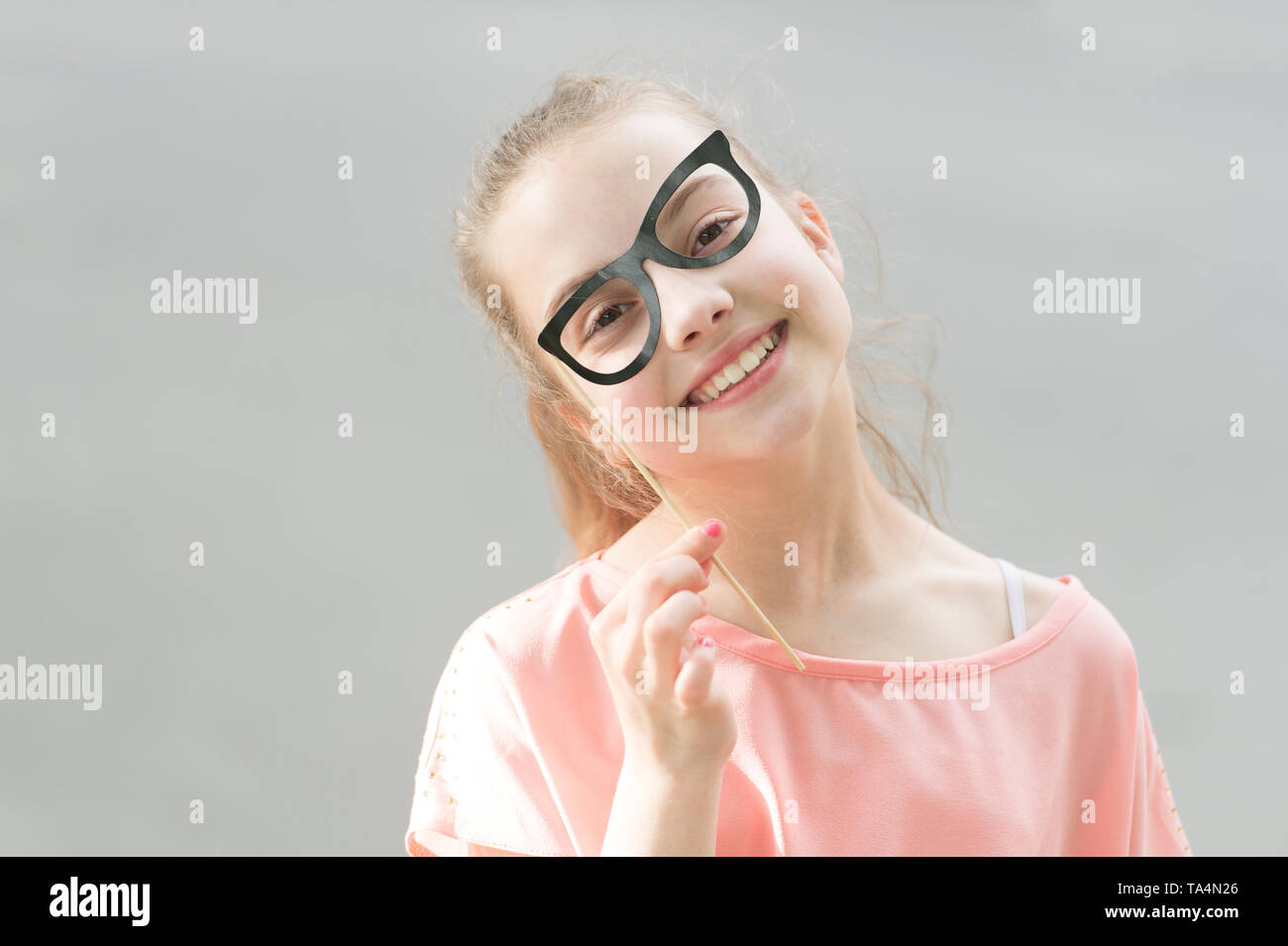 3be142a3d6d6 Small smiling girl with funny look through prop glasses. Happy little child  with adorable face shining with happiness. Children bring so much happiness.