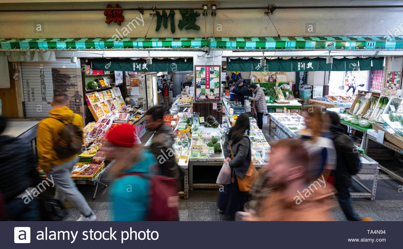 Crowds of people walking past shop selling fresh produce in Nishiki Market, Higashiuoyacho, Nakagyo-ku, Kyoto, Honshu, Japan - Stock Image