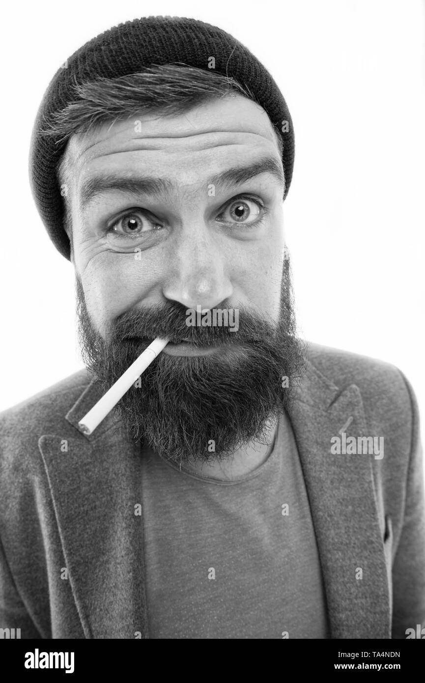 Hipster brutal bearded tobacco smoker. Man brutal bearded hipster dressed as vagabond smoking cigarette. Brutal unshaven guy smoking isolated white background. Brutal habits and lifestyle of tramp. - Stock Image