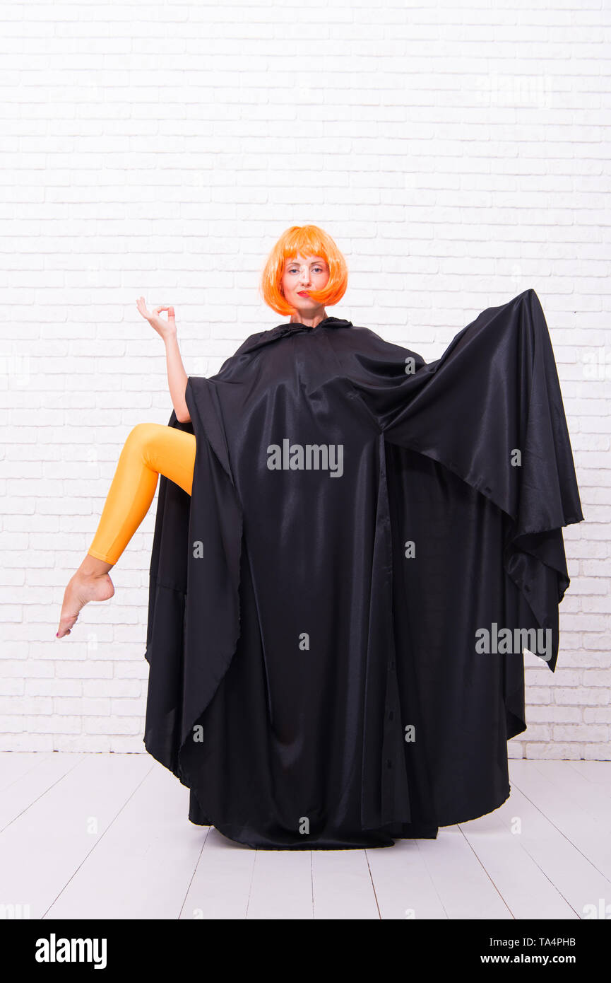 Enjoyment in motion. Feel your body. Dancing theatre performer. Dancing in cloak. Girl with long fit legs in orange tights dancing. Woman ginger wig performing modern art dance. Dancer lifestyle. - Stock Image
