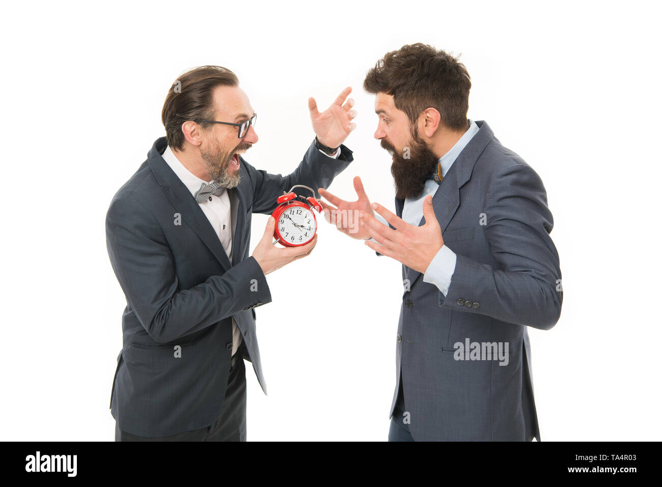 time management. mature bearded men in formal suit hold alarm clock. deadline. late again. angry businessmen. bad morning. a lot of work. Time is money. watching the time. checking the time. - Stock Image