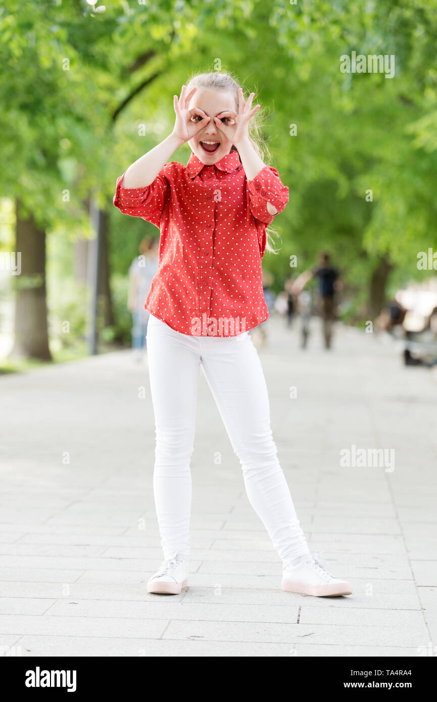 Girl carefree child. Kid walking sunny day. Summer holidays. Emotional kid in park nature background. Charming stylish fashionable girl in park. Little child enjoy walk in park. Weekend walk. - Stock Image