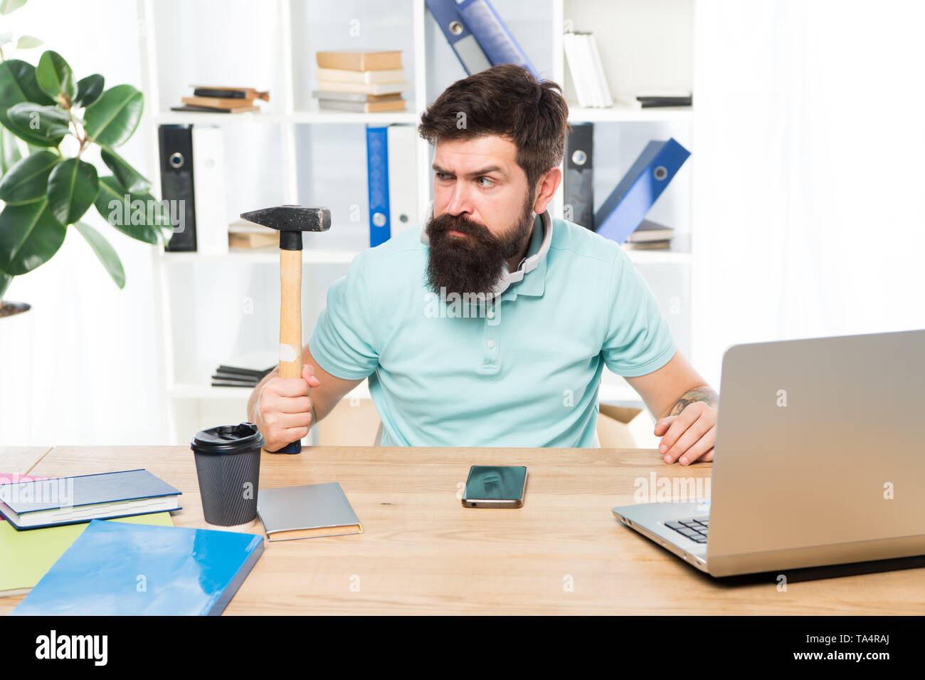 Office life makes him crazy. Businessman with beard and mustache gone mad with hammer in a hand. Angry aggressive businessman in office. Frustrated office worker holding hammer poised ready to smash. - Stock Image