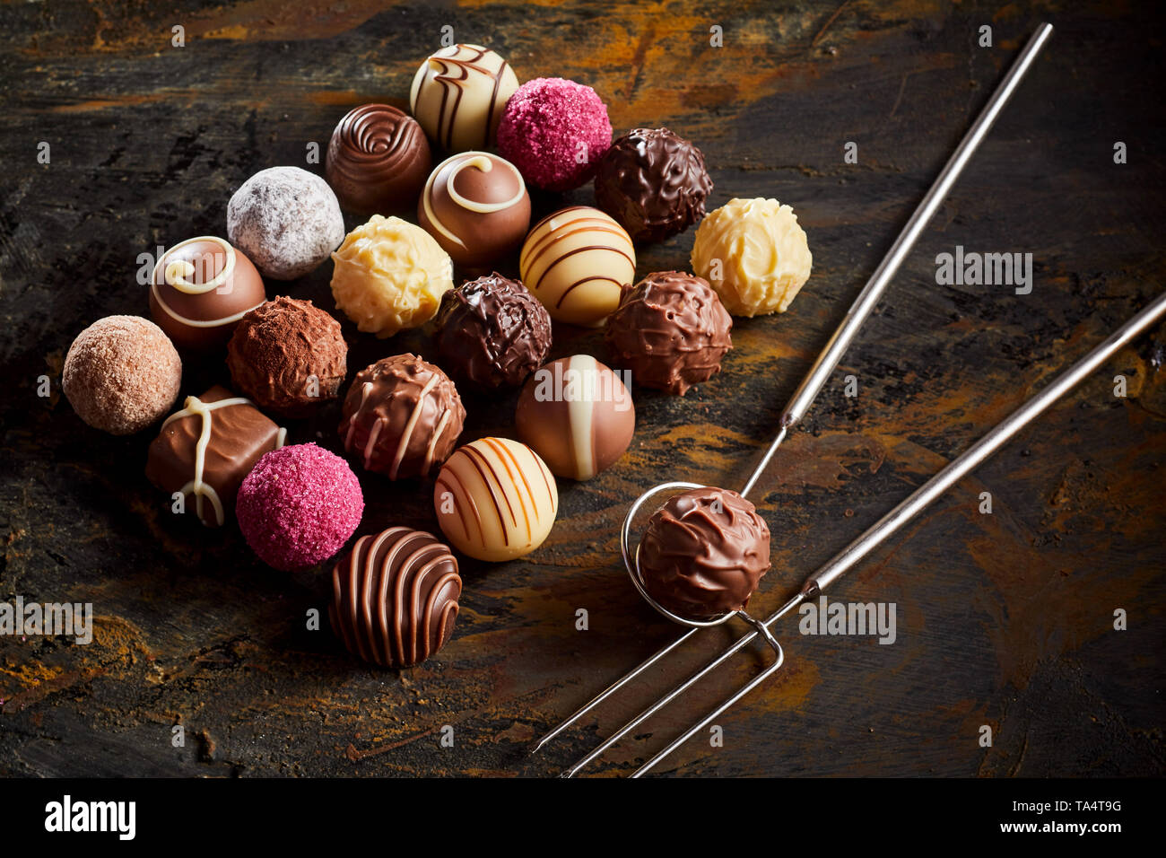 Handmade chocolate praline bonbon display with a neat rectangle of assorted fondants on rustic wood with wire lifter and fork Stock Photo