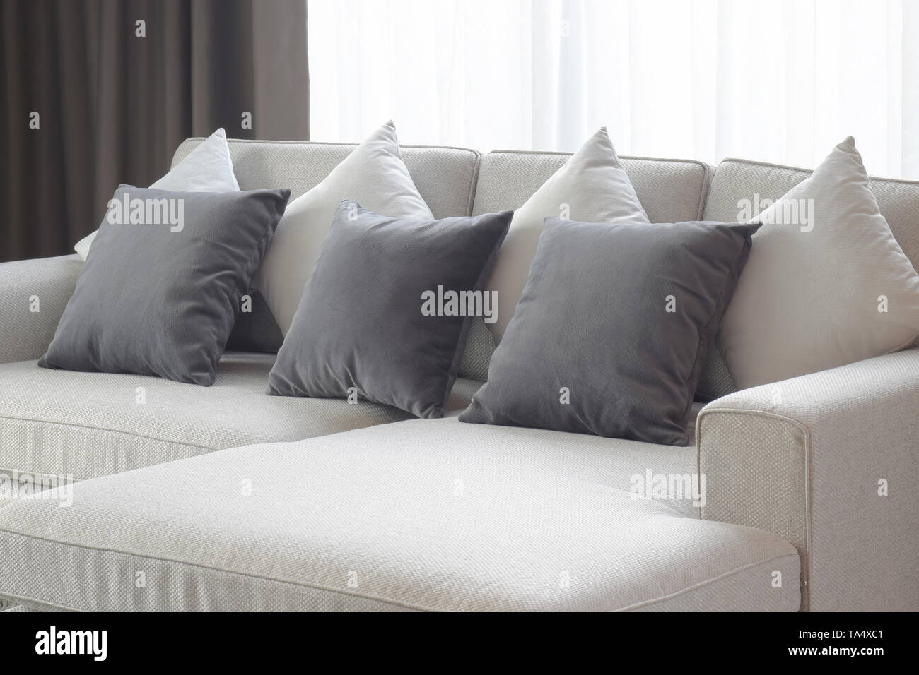 Two tone pillows lay on beige sofa in living room - Stock Image