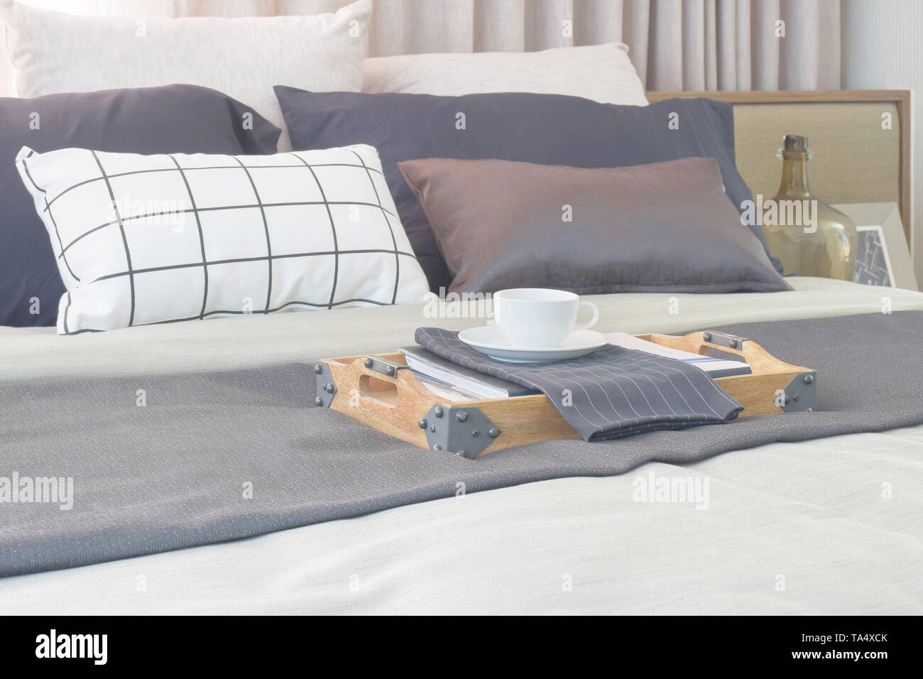 Coffee cup in wooden tray setting on bed in modern classic style interior bedroom - Stock Image
