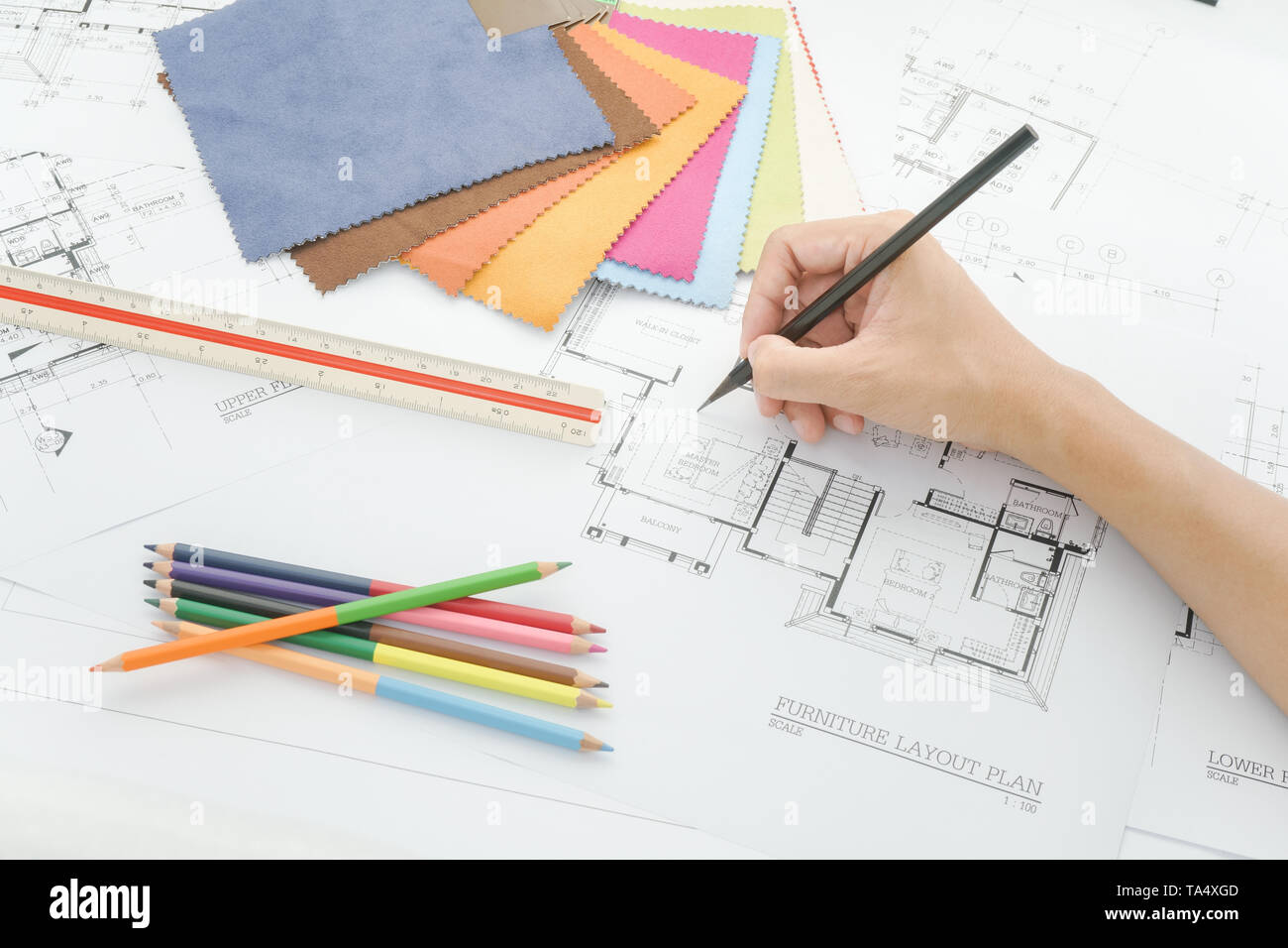 Hand writing on architectural plan with fabric sample on interior designer working table - Stock Image