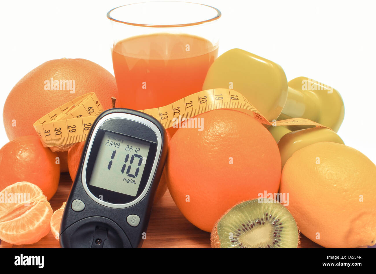 Glucose meter for checking sugar level and fresh ripe natural fruits with tape measure, concept of diabetes, slimming and healthy nutrition - Stock Image