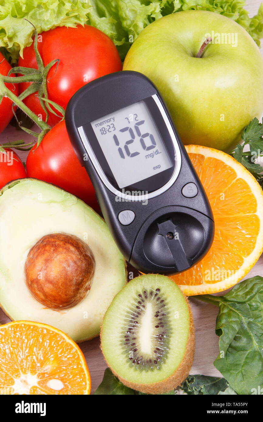 Glucometer with result of sugar level and healthy fruits and vegetables. Nutritious food containing natural minerals and vitamins during diabetes - Stock Image