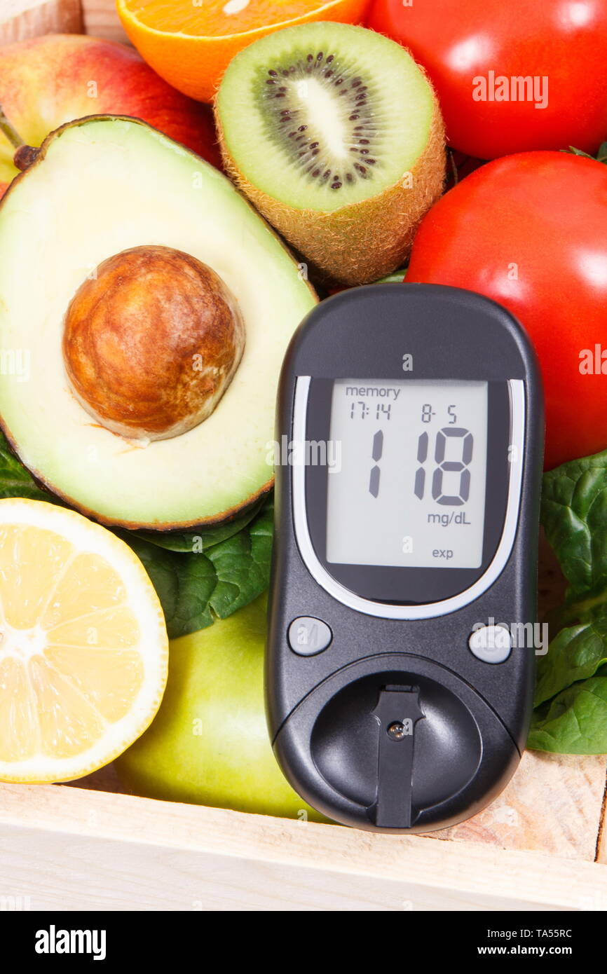 Glucometer for measuring sugar level and fresh ripe fruits with vegetables as healthy nutritious snack containing natural vitamins - Stock Image
