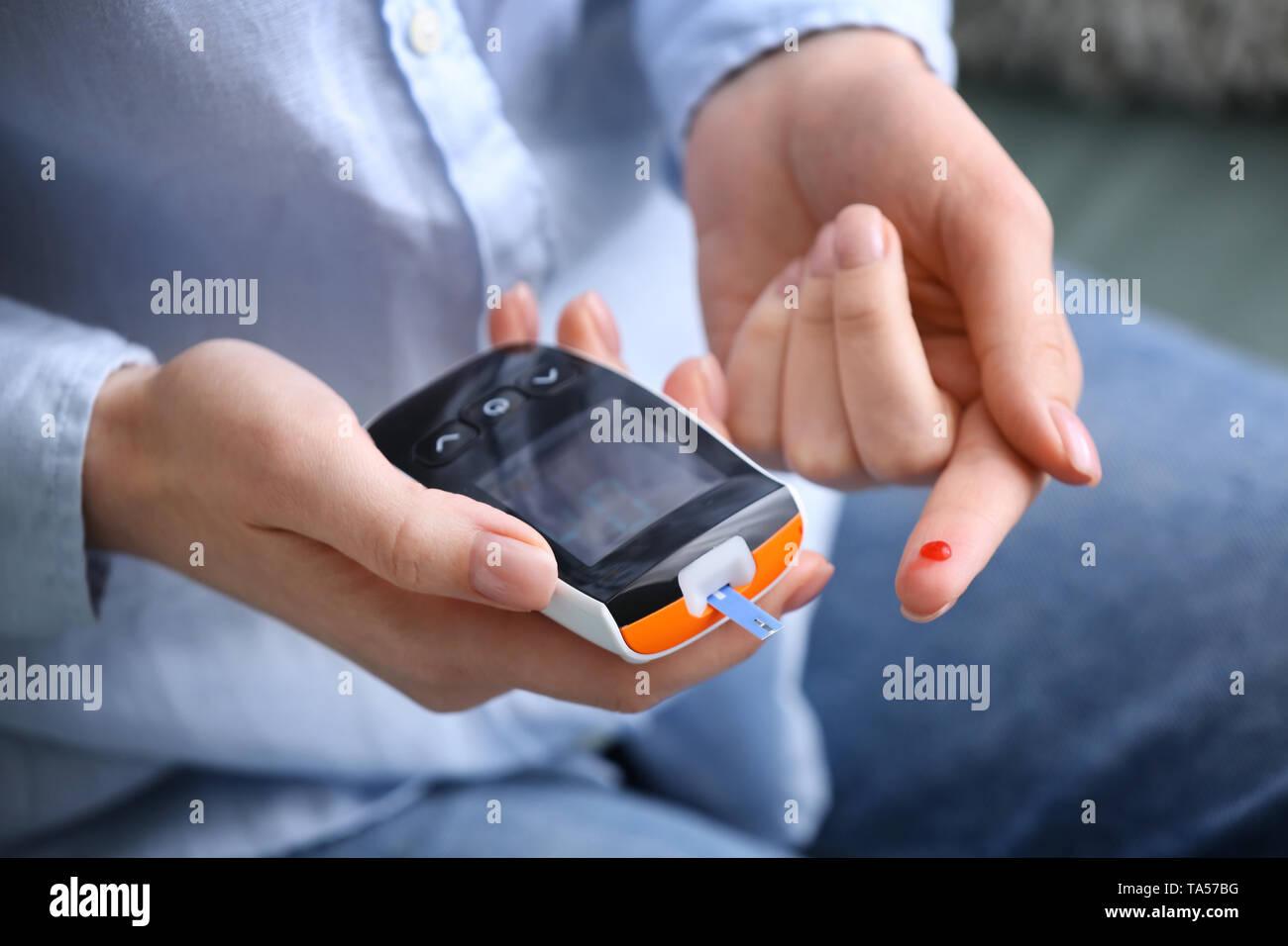 Diabetic woman using digital glucometer, closeup - Stock Image