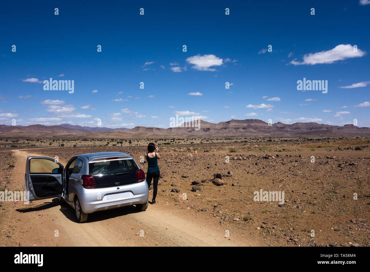 Young female tourist photographing on a dirt road with some rocky desert landscape on a road-trip from Marrakesh to Merzouga, Morocco Stock Photo