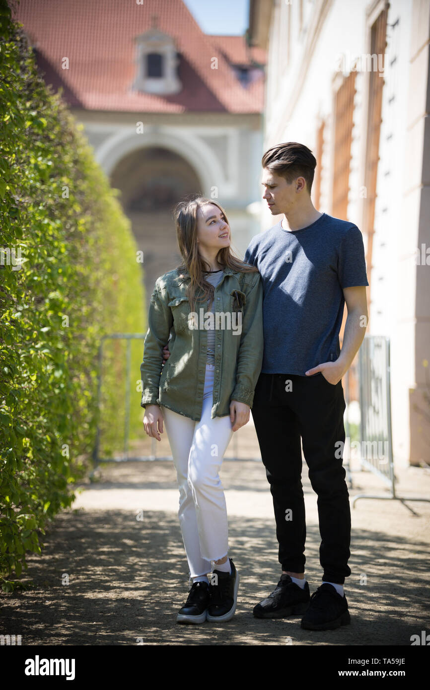 A young couple traveling. Standing on the street and look at each other. Mid shot Stock Photo