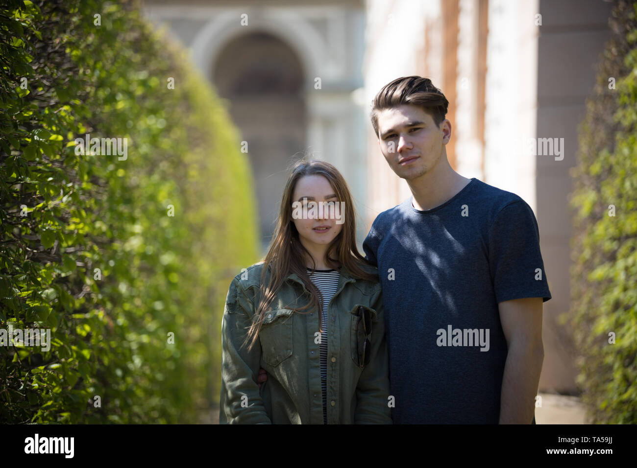 A young couple traveling. Standing on the street and looking in the camera. Mid shot Stock Photo