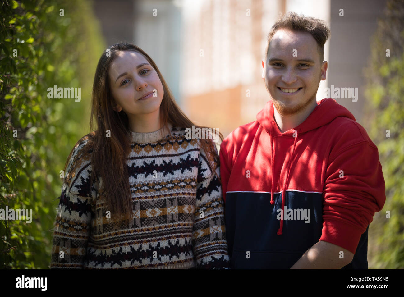 A young smiling couple standing in green park. Mid shot Stock Photo