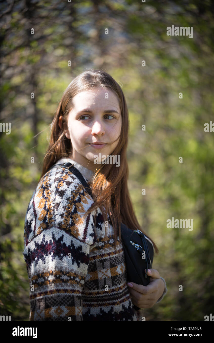 A young woman standing in green park holding a waist bag. Mid shot Stock Photo