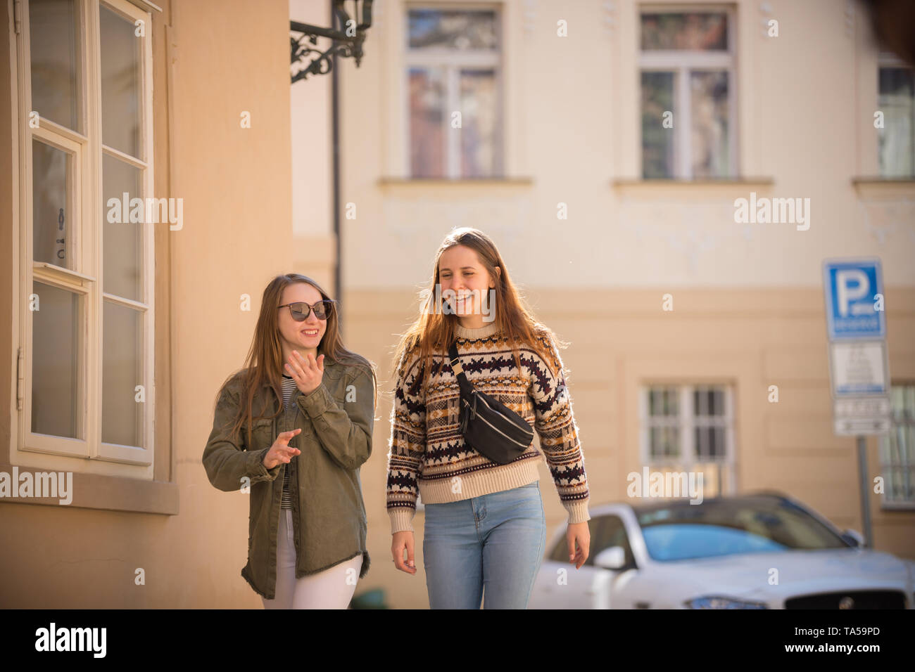 Two young smiling women walking on the streets. Mid shot Stock Photo