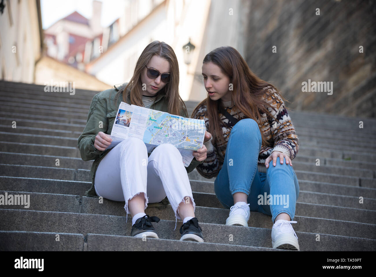 Two young traveling women sitting on stairs and looking at the map. Mid shot Stock Photo