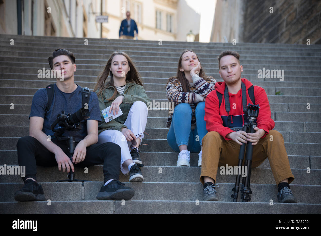 Young traveling people sitting on the stairs. Men holding shooting equipment. Mid shot Stock Photo