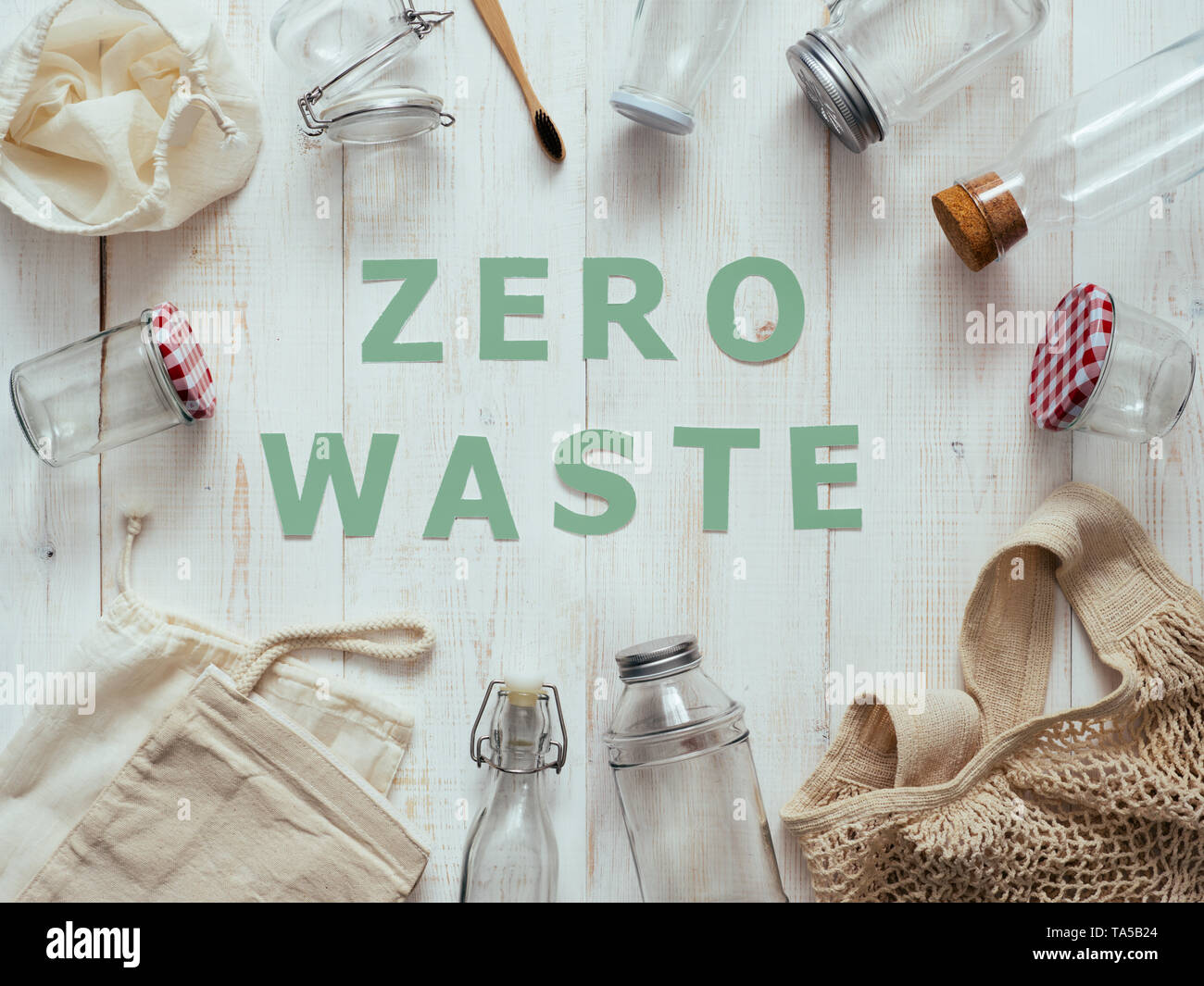 Zero waste concept. Textile eco bags, glass jars and bamboo toothbrush on white wooden background with Zero Waste green paper text in center. Eco frie - Stock Image