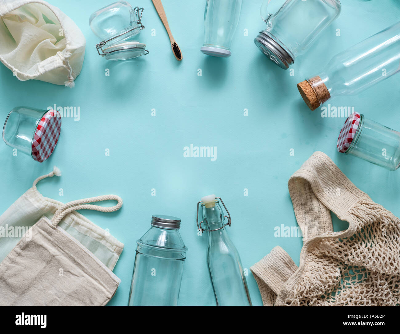 Zero waste concept. Textile eco bags, glass jars and bamboo toothbrush on blue background with copy space for text in center. Eco friendly and reuse c - Stock Image