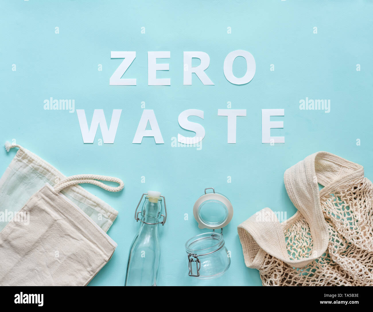 Zero waste concept. Textile eco bags, glass jar and bottle on blue background with Zero Waste white paper text. Eco friendly and reuse concept. Top vi - Stock Image