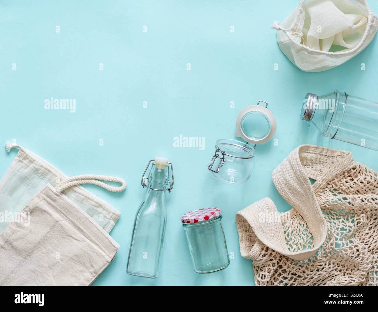 Zero waste concept. Textile eco bags, glass jars and glass bottles on blue background with copy space for text or design. Eco friendly and reuse conce - Stock Image