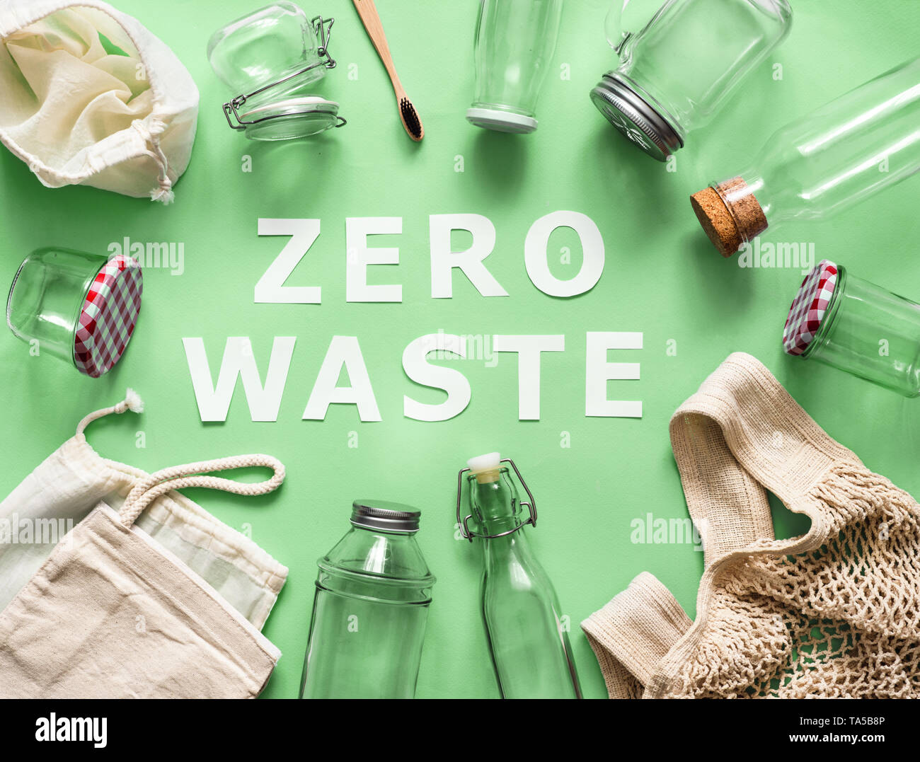 Zero waste concept. Textile eco bags, glass jars and bamboo toothbrush on green background with Zero Waste white paper text in center. Eco friendly an - Stock Image