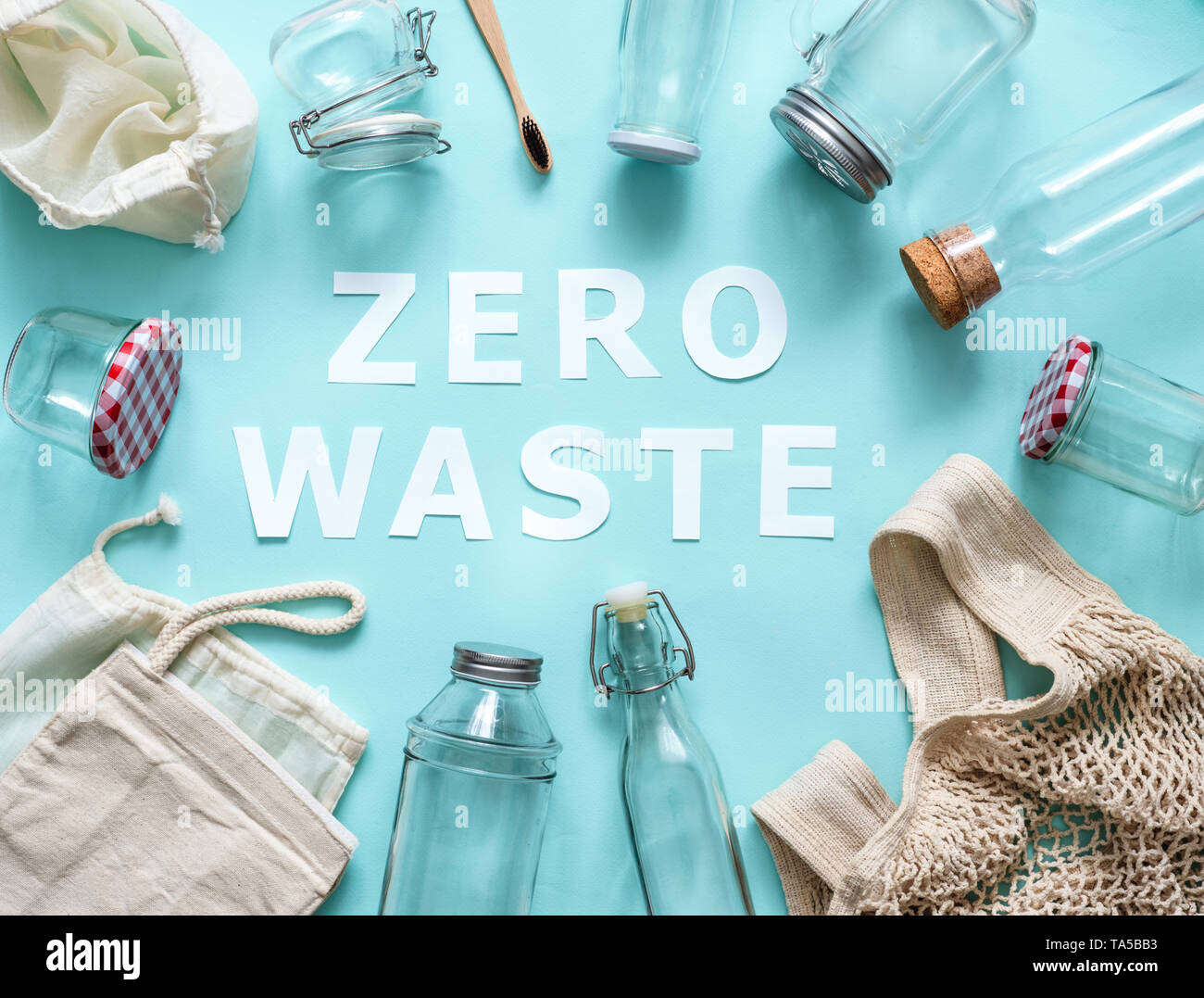 Zero waste concept. Textile eco bags, glass jars and bamboo toothbrush on blue background with Zero Waste white paper text in center. Eco friendly and - Stock Image