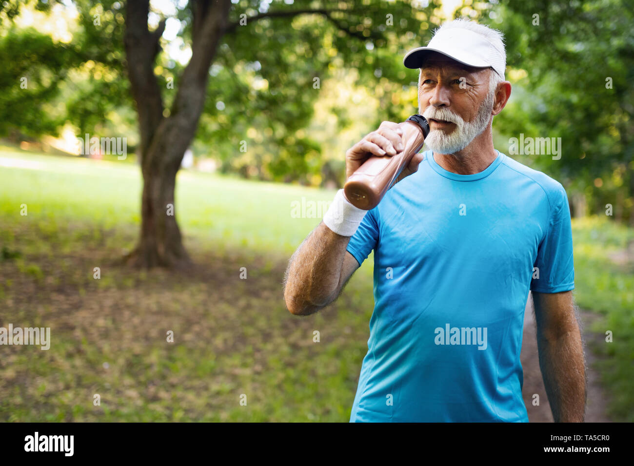 Handsome senior man resting after jog at the park on a sunny day. - Stock Image
