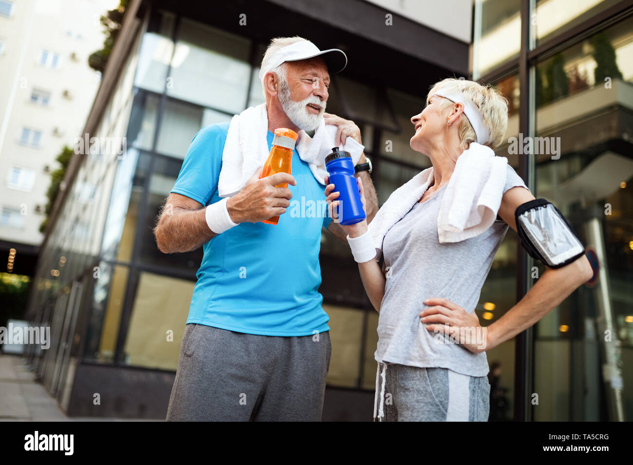 Mature couple drinks water to replenish energy and to hydrate - Stock Image
