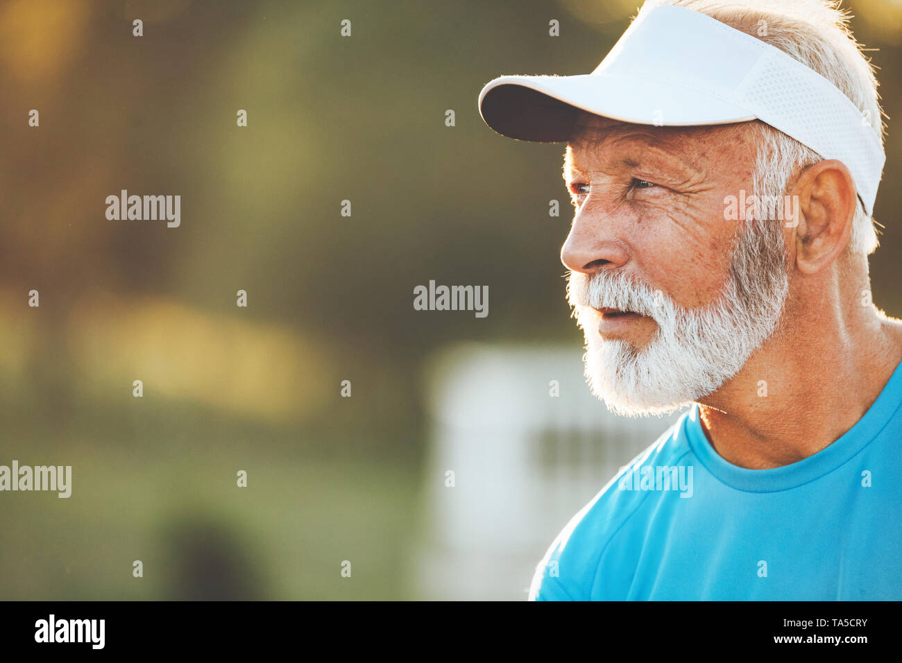 Portrait of athletic mature man after run. Handsome senior man resting after jog at the park - Stock Image