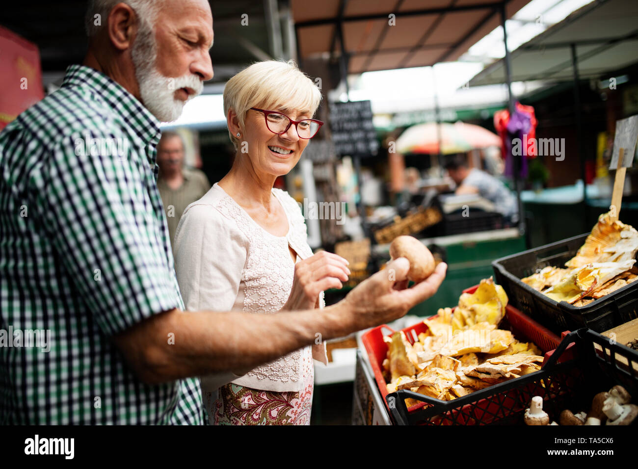 Senior couple buying fresh vegetables and fruits at the local market - Stock Image