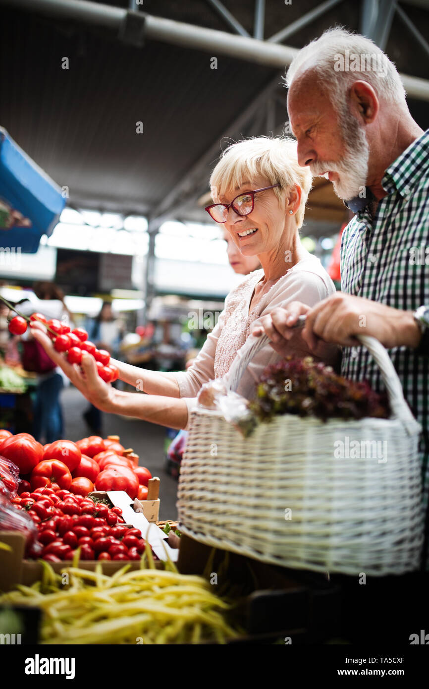 Shopping, food, sale, consumerism and people concept - happy senior couple buying fresh food - Stock Image