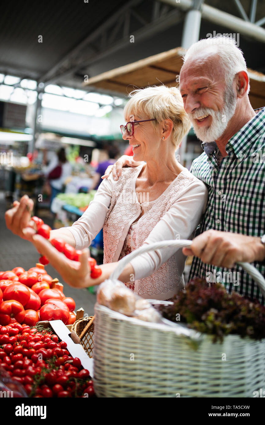Senior family couple choosing bio food fruit and vegetable on the market during weekly shopping - Stock Image