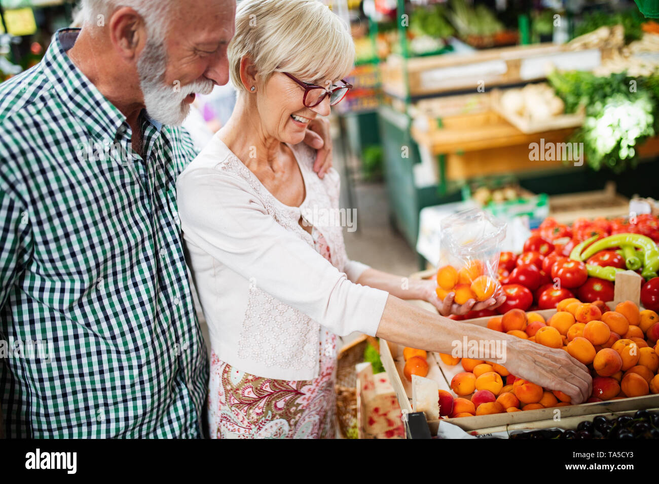 Senior shopping couple with basket on the market. Healthy diet. - Stock Image