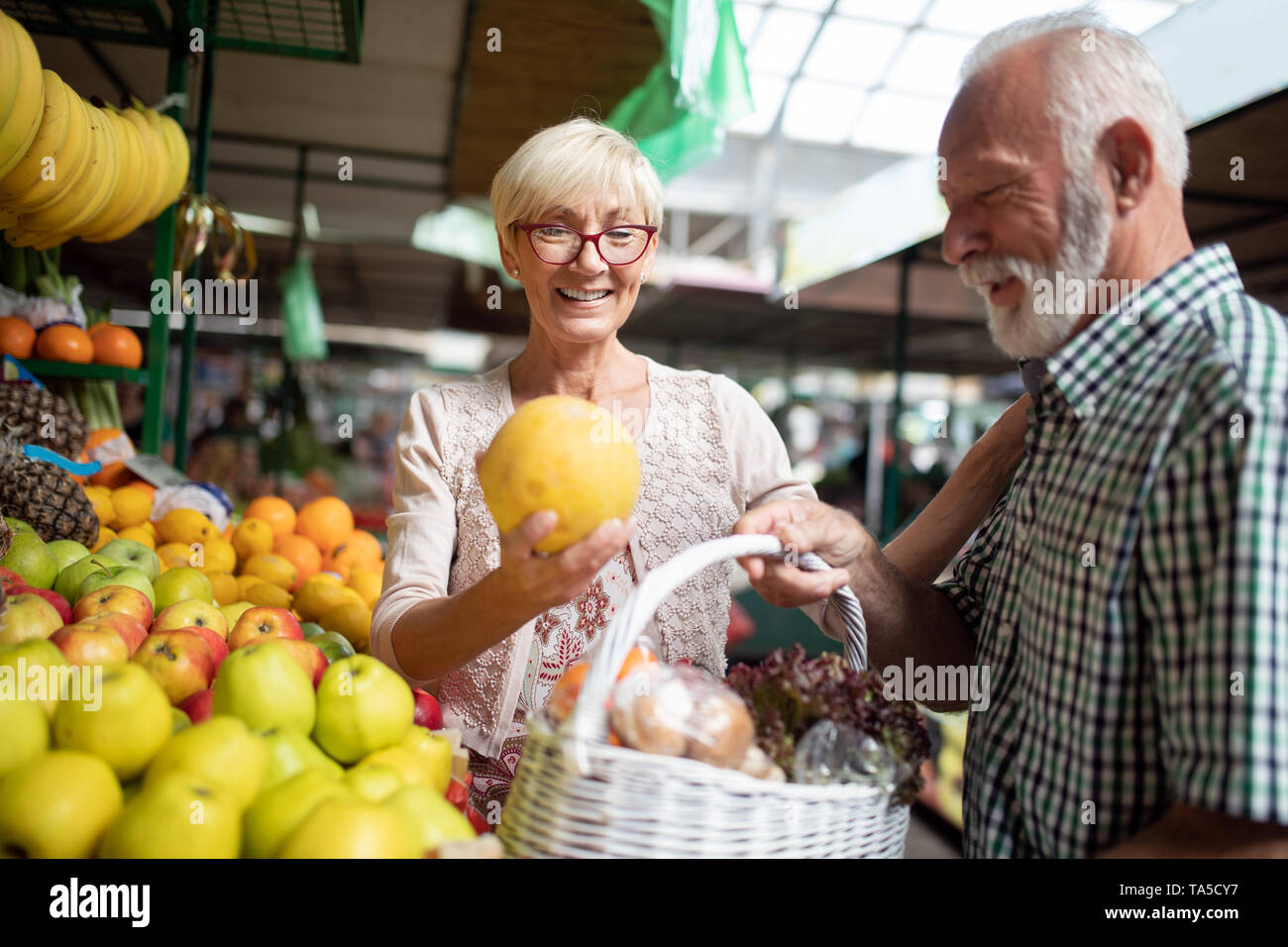 Portrait of beautiful elderly couple in market buing food - Stock Image
