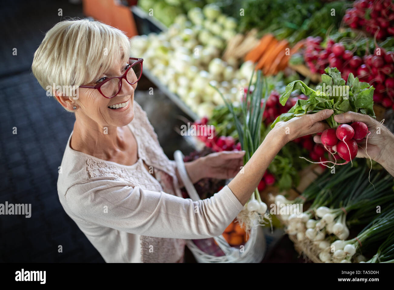 Senior woman buying vegetables at the green market. - Stock Image