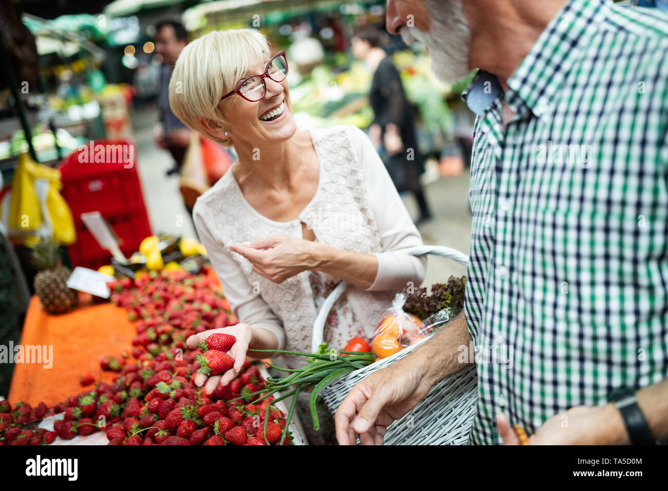 Picture of senior couple at marketplace buying vegetables - Stock Image