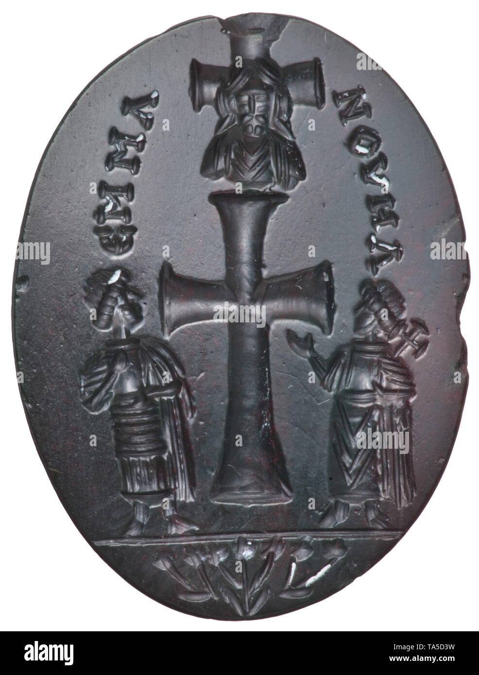 An early Byzantine intaglio depicting the Princes of the Apostles, 6th - 7th century Dark, semi-precious stone, the discolouring possibly deliberate due to the application of heat in antiquity. Cross flanked by Peter and Paul, above the bust of Christ in front of a smaller cross. Bouquet of flowers with seven petals incised below. On the side the appellation of Christ, 'Emmanuel', in Greek letters. Exceptionally high quality Byzantine intaglio with a rare motif. Length 2 cm. Provenance: Viennese private collection, acquired in the art trade durin, Additional-Rights-Clearance-Info-Not-Available - Stock Image