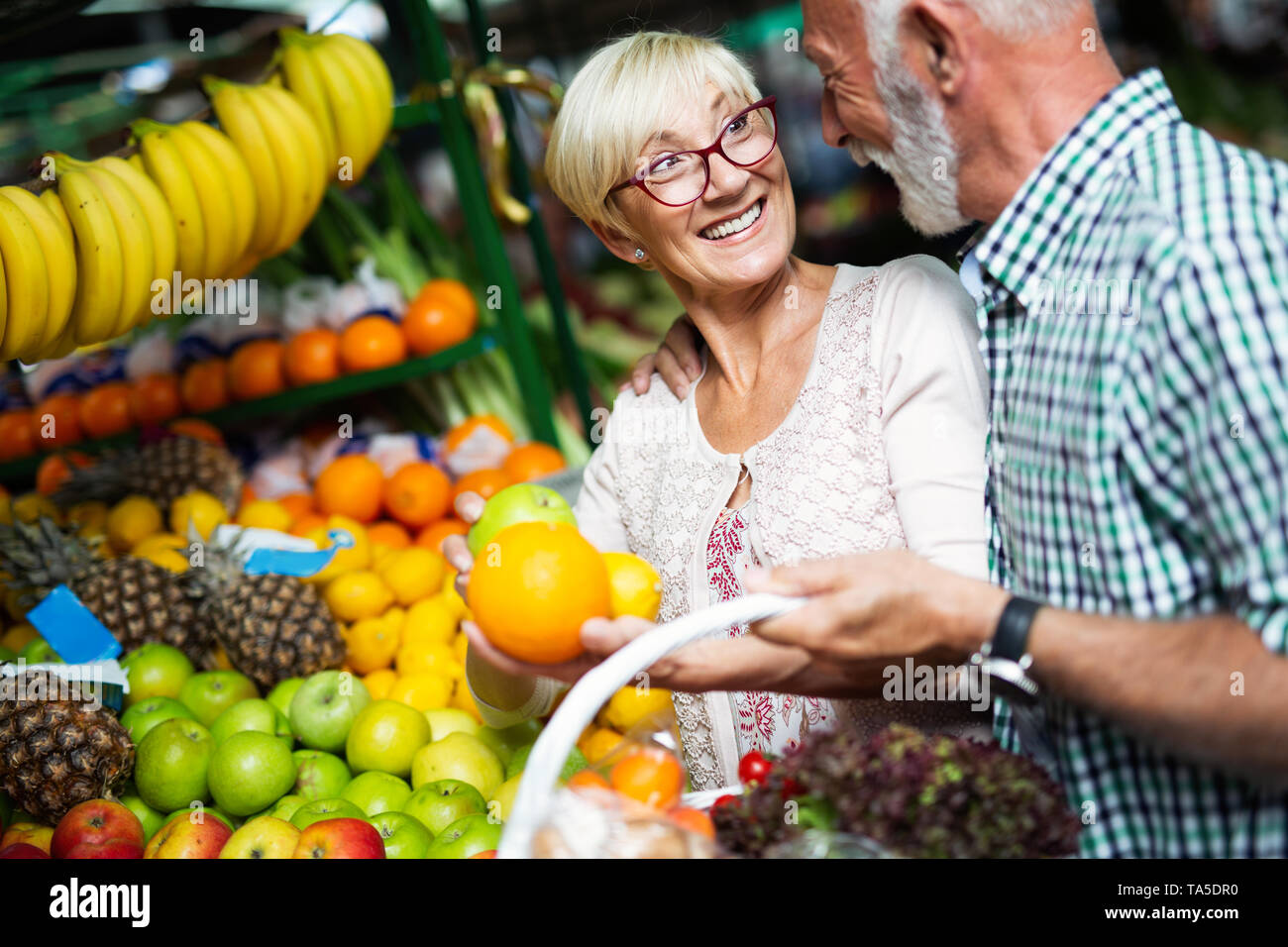 Beautiful senior couple choosing health products in the market - Stock Image
