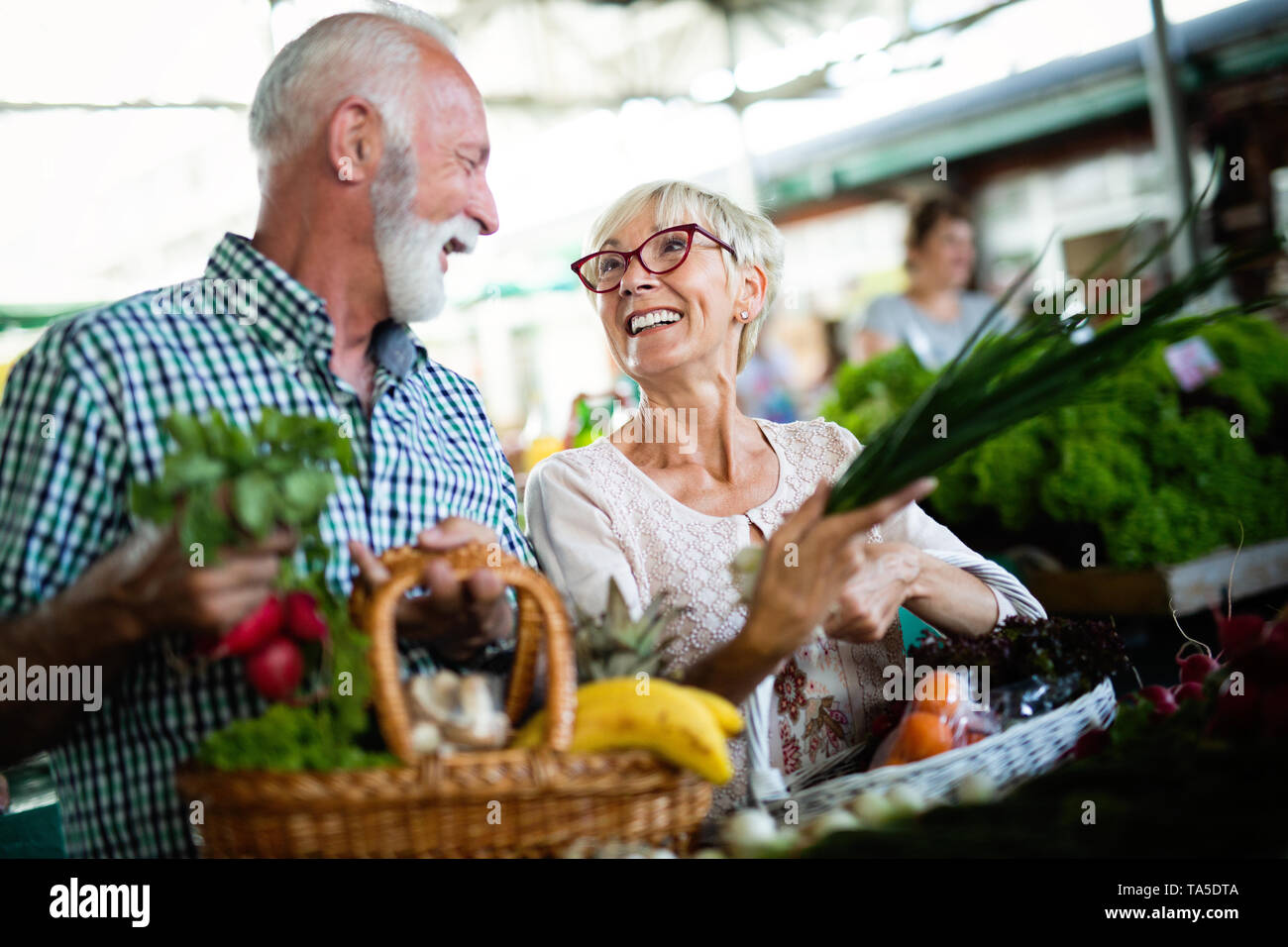 Happy senior couple with basket at the local market - Stock Image