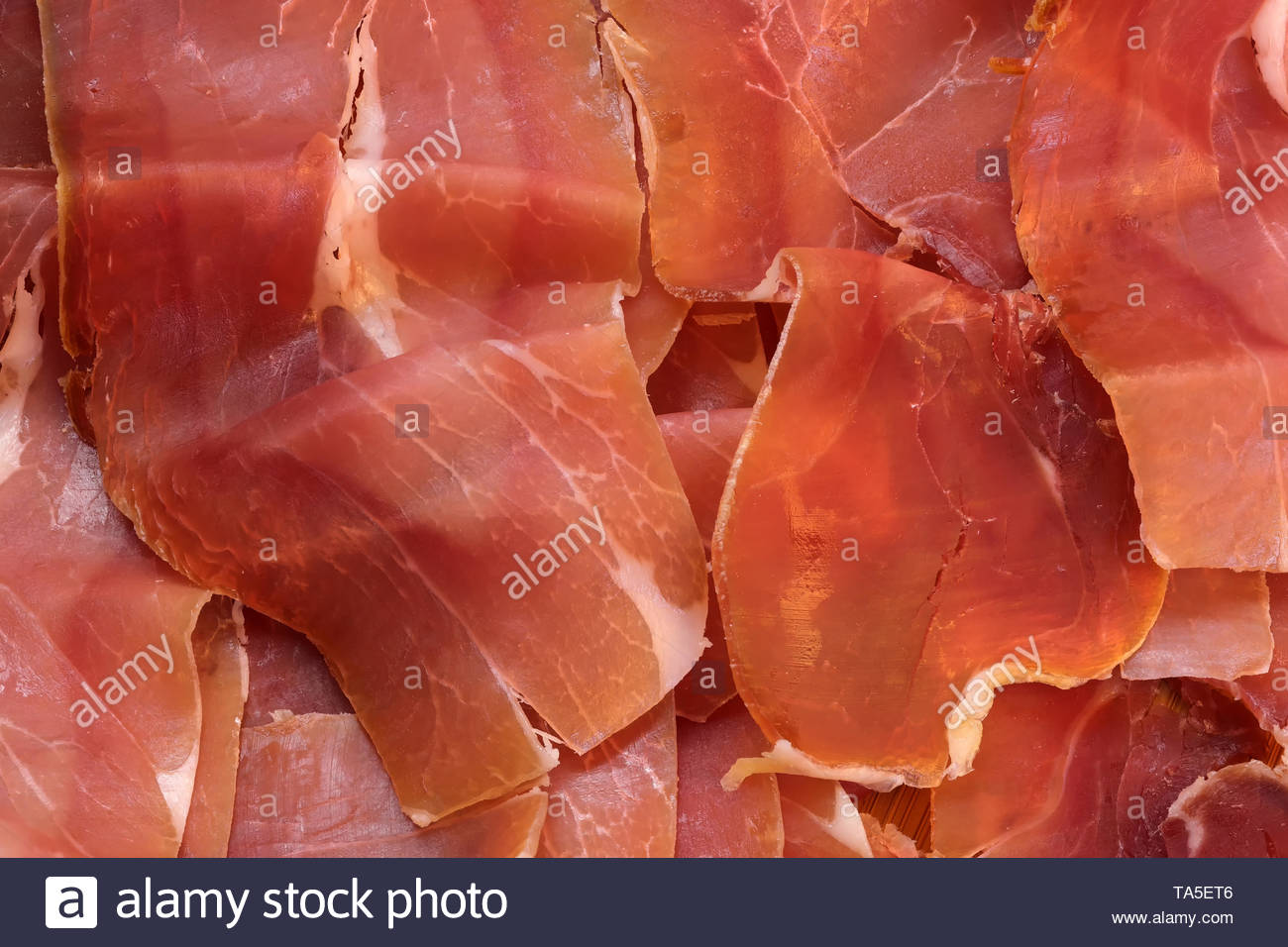 Dried red meat, jamon cut into thin ribbons close-up macro photo background from food - Stock Image