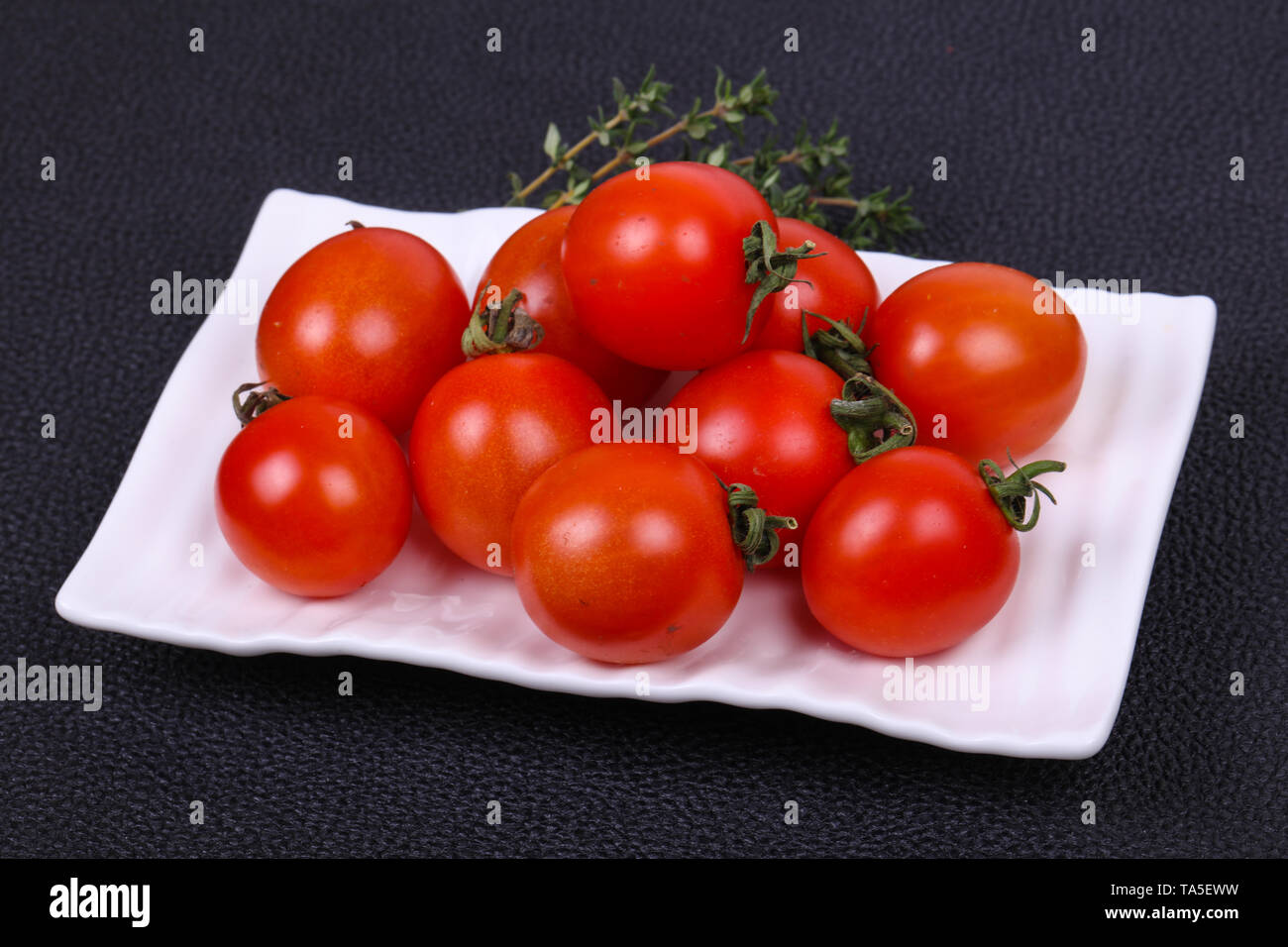 Cherry tomato in the bowl served thyme branch - Stock Image
