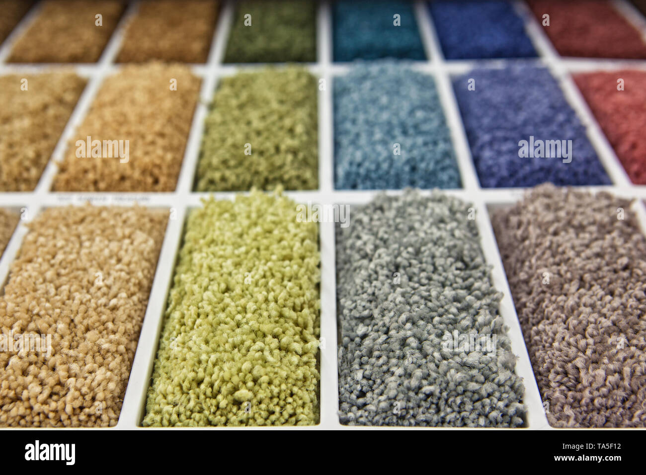 samples of multi-colored carpets on the shelves - Stock Image