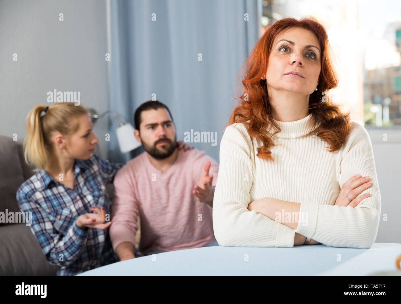 Young serious couple has a family stressful conversation at home - Stock Image