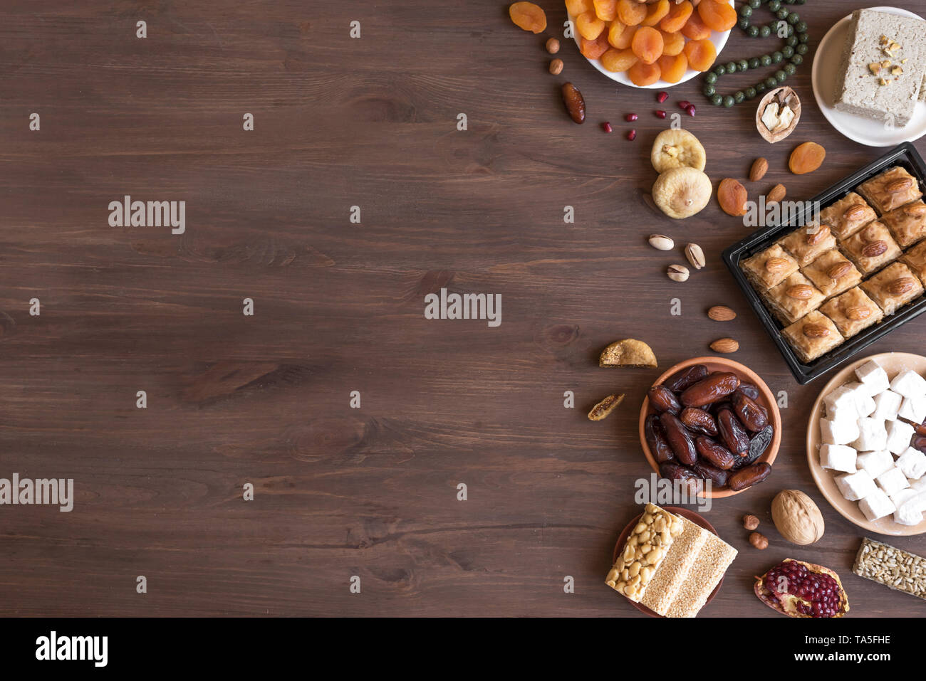 Assortment, set of Eastern, Arabic, Turkish sweets, nuts and dried fruits on wooden table, top view, copy space. Holiday Middle Eastern traditional sw - Stock Image